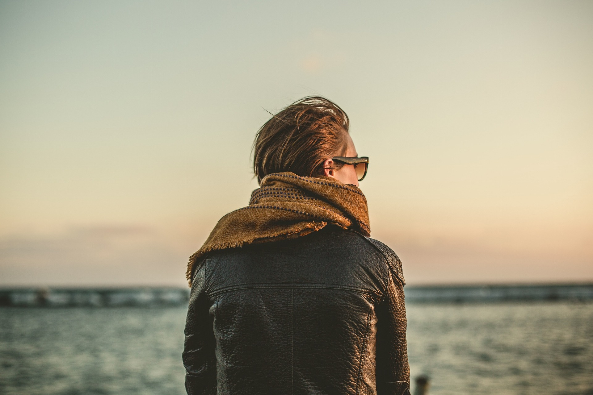 Back of person wearing a leather jacket and scarf while looking at the ocean
